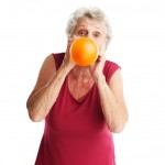 senior woman blowing balloon