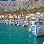 Colorful Makarska boats and waterfront under Biokovo mountain view, Dalmatia region of Croatia