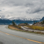 The Seward Highway curves beneath cloudy skies as it passes by snow-covered mountains at the edge of an ocean inlet south of Anchorage.