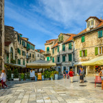 Tourists enjoy cafes and shops on an early autumn afternoon on the Fruit Square in the Diocletian's Palace section of Old Town Split, Croatia.