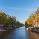 Veiw on the bridge through the river channel with boat, typical picture of canals in Amsterdam, The Netherlands.