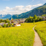 Beautiful view of green alpine meadow with a walking path and village St. Gilgen, Austria. Alpine landscape.