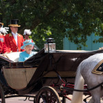 Queen Elizabeth II travels along The Mall in an open carriage pulled by horses, on her way from Buckingham Palace