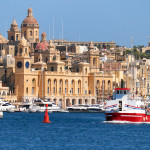 View of historical buildings of Birgu across the Dockyard creek with Cruises ship passing along the coast, Malta