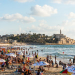 Lots of tourists and locals are swimming at blue Mediterranean sea and spending their vacation at the beach of Tel Aviv, Israel in summertime.