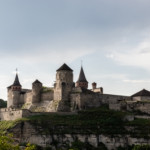 Medieval Kamianets-Podilskyi fortress of the XVI century on a rocky green hill under the evening cloudy sky. Ukraine